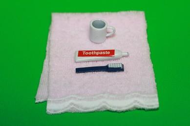 Handtuch, Zahnbürste, Becher und Zahnpasta
