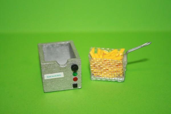 Fritteuse mit Korb und Pommes Frites