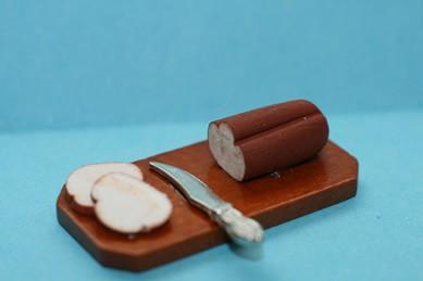 Holzbrett mit Brot, Brotscheiben und Messer